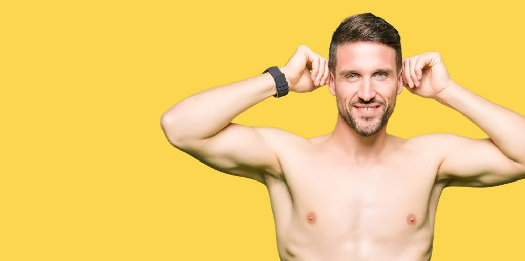 White Man Holds Out Ears with Shirt Off in Front of Yellow Background